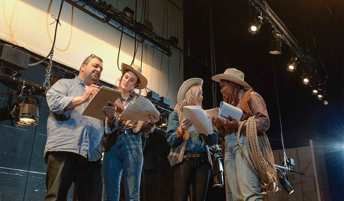 Professor Richard Perez stands on a stage without a set, with cast members Sam Hill Class of 2018, Olivia Lehnertz Class of 2019 and Akia Smith Class of 2018. The three women are wearing western costumes including cowboy hats and boots, denim, plaid, and vests. Akia holds a lasso. Another coil of rope is in the foreground on the floor.