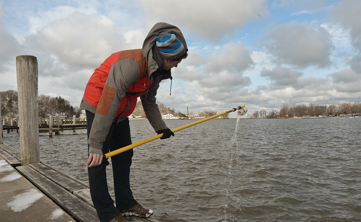 A Hope College student standing on a pier in the winter takes a water sample from Lake Macatawa. He holds a receptacle at the end of a long yellow pole to dip into the water.