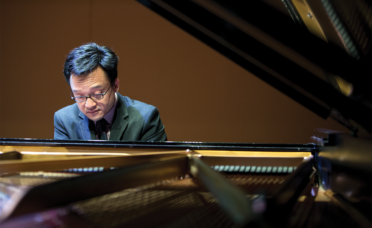 Dr. Andrew Le plays piano. Wearing glasses and a blazer, we see Dr. Lee from the opposite end of a grand piano, through the open lid, beyond the strings.