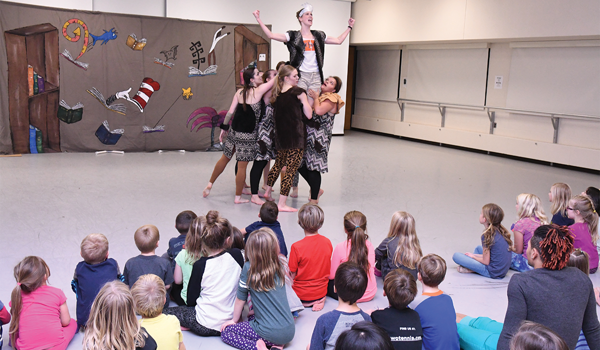 Five student dancers hoist a sixth in the air, in front of an audience of school children, as part of the StrikeTime Dance Theatre's production which brings to life a Dr. Suess story.