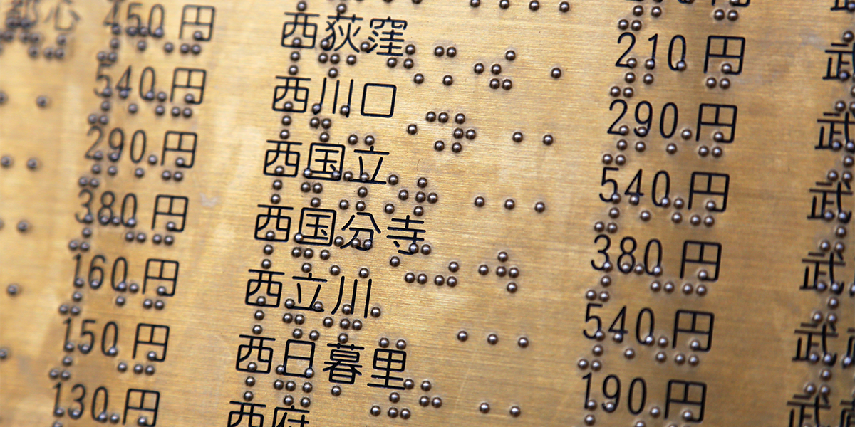 An engraved brass plate is shown with Arabic numbers, Japanese translation, and braille accompanying each.