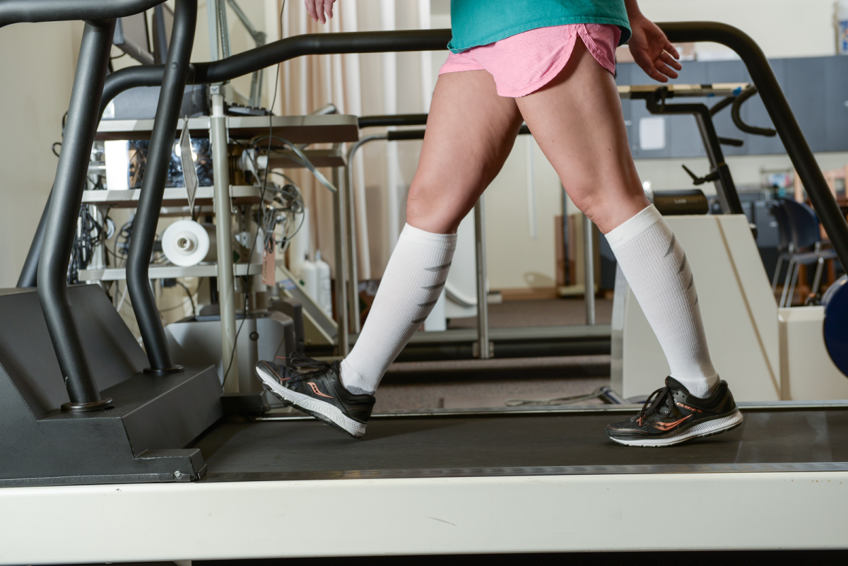 A woman, shown from the waist down, wearing pink shorts, black running shoes, and white knee-high compression socks walks on a treadmill.
