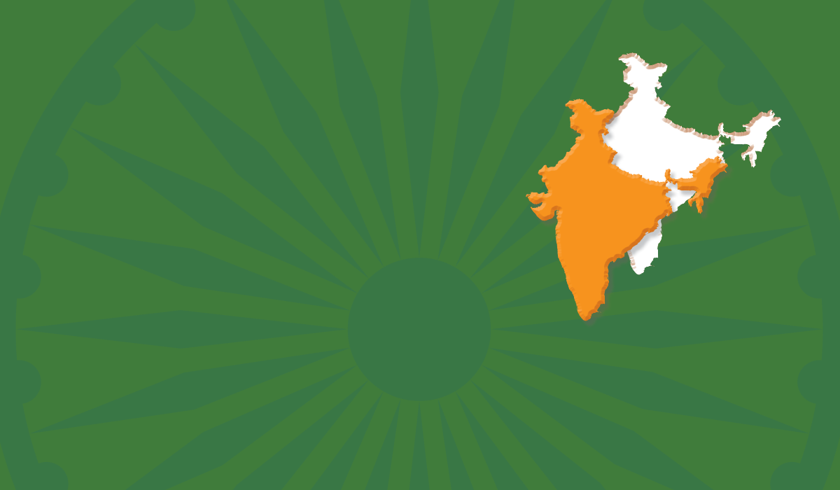 An Ashoka Chakra, the 24-spoke wheel featured in the center of the flag of India, is overlaid with a field of India green, with a saffron color shape of India cut out from the green and offset, leaving a hole in the green field.