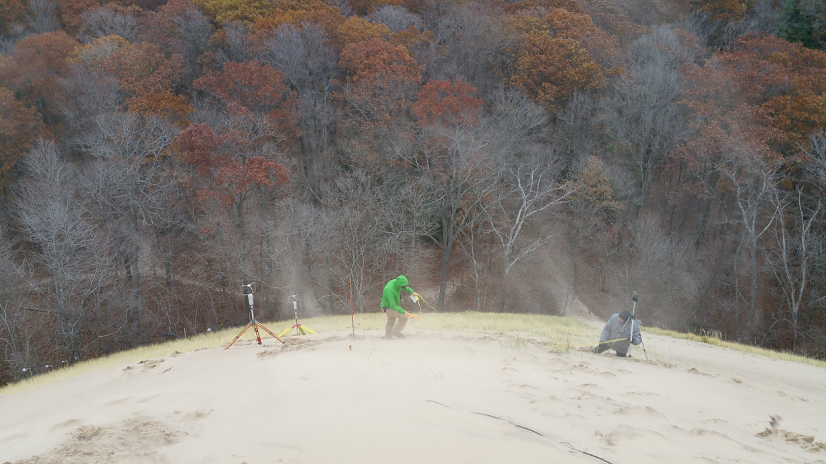 Two geologists set up ultrasonic anemometers on the side of a very windy beach dune. Sand swirls around them. Leafless and fall-color trees are in the background.
