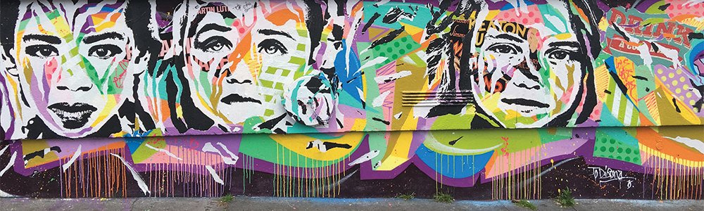 Mur Rue Alibert, by Jo Di Bona. A backdrop of bright, classic graffiti shapes, paint drips intermingling the colors, is overlaid by three separate black and white printed faces. The printed faces of a woman and two young girls have sections torn out, revealing the bright colors and shapes behind them.