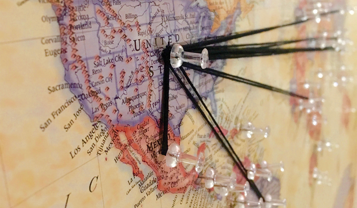 A map of the world, with the United States in the foreground, uses thumb tacks and yarn to represent the concept of global immigration to the US.
