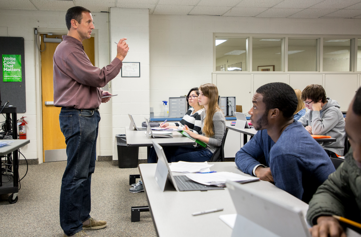 Dr. Ryan McFall stands at front of computer science classroom. Students with laptops on the table in front of them look on attentively, while taking notes. A green poster in the background reads 'Write Code that Matters'.