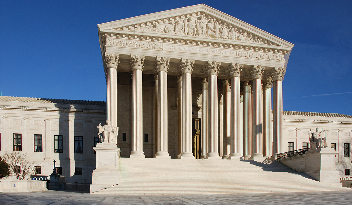 United States Supreme Court Building on a sunny day, with blue cloudless sky in the background. The Supreme Court Building is built in the Neoclassical style. The public façade is made of marble quarried from Vermont, and features 24 columns.